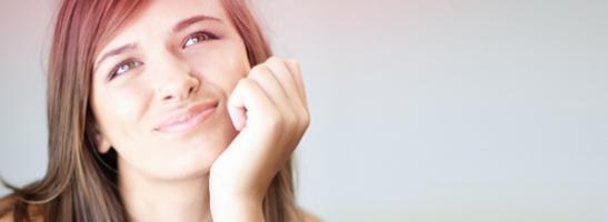 Bilde av en ung kvinne ser tankefull. Bildet illustrerer at det er vanlig å ha mange problemstillinger knyttet til puberteten, om menstruasjon eller tamponger.