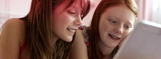 Bilde av to unge jenter sitter foran en datamaskin. Bildet illustrerer at det er vanlig å ha mange spørsmål, og o.b.®'s hjemmeside kan du finne informasjon om første menstruasjon, pubertet og annen nyttig informasjon