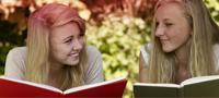 Bilde av to unge kvinner som leser boken. Bildet illustrerer de mange mytene som er forbundet med menstruasjon.